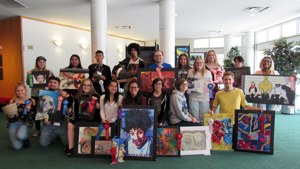 High school seniors pose with their artwork in a lobby.
